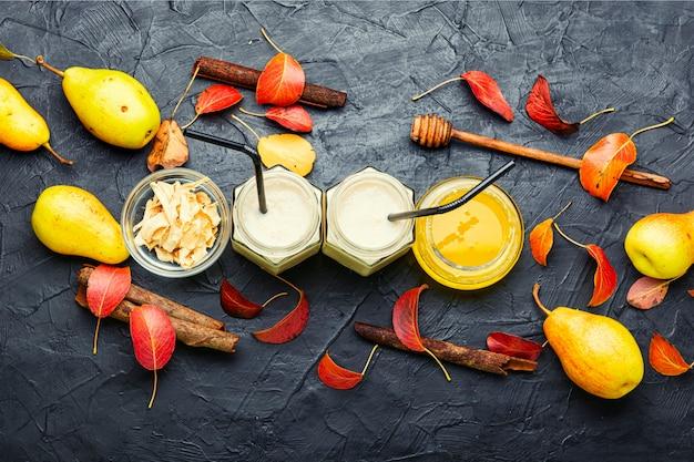 Smoothie de pera e gengibre e folhas caídas. jarra de smoothies de frutas