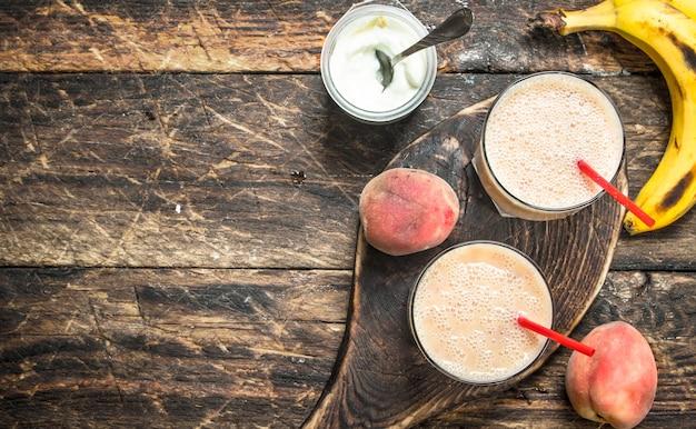 Smoothie de pêssego com iogurte e banana em um fundo de madeira