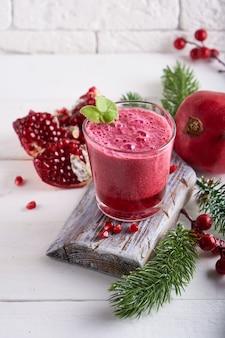 Smoothie de romã em um copo com ramos de abeto e decoração de natal