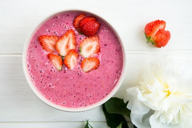 Smoothie de rosa saudável na tigela de banana e morangos com pedaços de bagas no topo