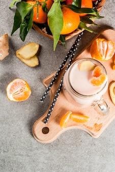 Smoothie de tangerina com gengibre em frasco de vidro com tangerinas cruas frescas em fundo de pedra cinza