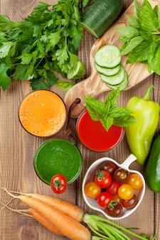 Smoothie de vegetal fresco na mesa de madeira. tomate, pepino, cenoura. vista do topo
