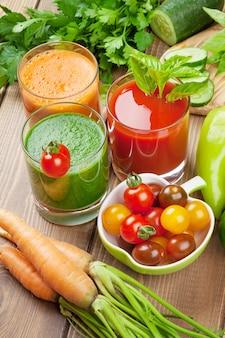 Smoothie de vegetal fresco na mesa de madeira. tomate, pepino, cenoura