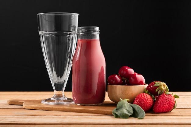 Smoothie de vista frontal e frutas com vidro
