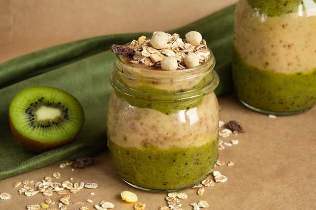 Smoothie em frasco de vidro: banana, kiwi, muesli. comida saudável, vegetariana
