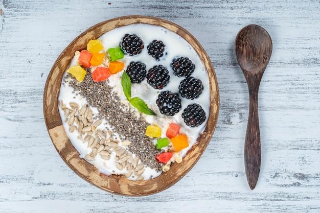 Smoothie em uma tigela de coco com amoras, aveia, sementes de girassol e sementes de chia no café da manhã, close-up. o conceito de alimentação saudável, superalimento. vista do topo