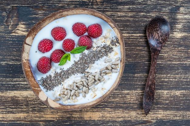 Smoothie em uma tigela de coco com framboesas, aveia, sementes de girassol e sementes de chia no café da manhã, close-up. o conceito de alimentação saudável, superalimento. vista do topo
