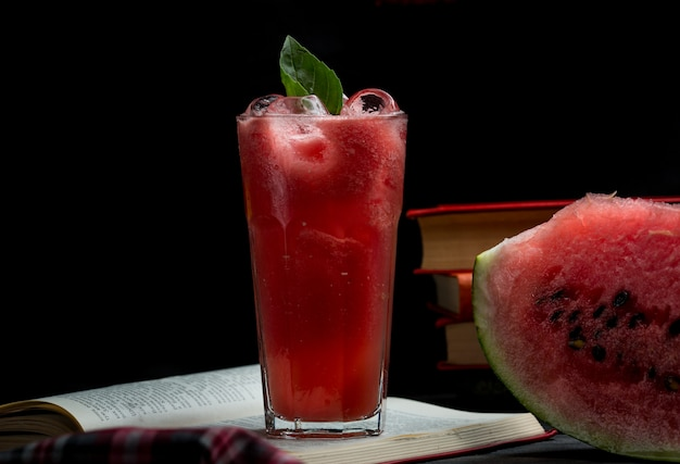 Smoothie gelado de melancia com folhas de hortelã e uma fatia de melancia