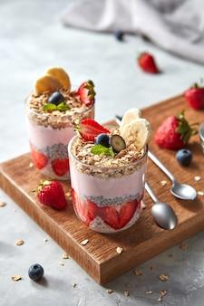 Smoothie rosa saudável em copos com frutas naturais, morango, banana, mirtilo
