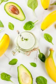 Smoothie saudável com banana e bebê espinafre n fundo de mármore branco