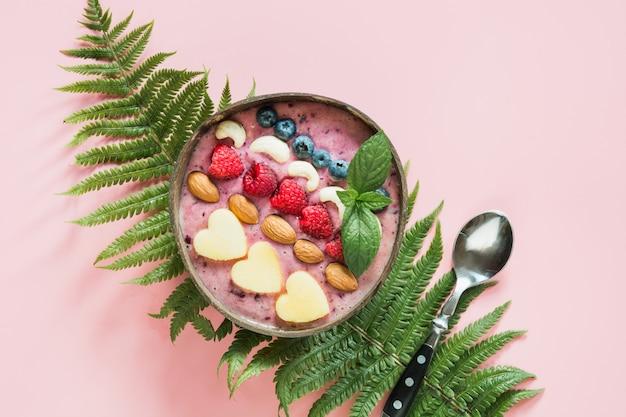 Smoothie saudável de banana e mirtilo café da manhã, decorado com frutas em uma tigela de coco em rosa.
