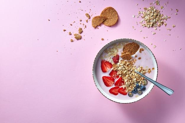 Smoothie saudável em tigela branca com frutas naturais, flocos de aveia e biscoitos