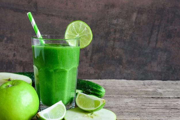Smoothie saudável verde em um copo com espinafre, maçã, pepino e limão com um canudo. bebida desintoxicante