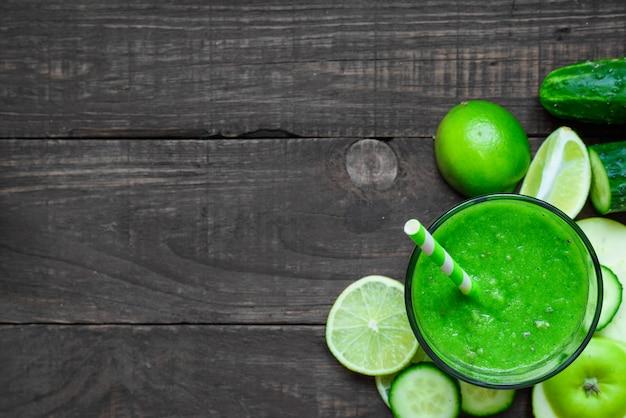 Smoothie saudável verde em um copo com espinafre, maçã, pepino e limão com um canudo sobre a mesa de madeira rústica