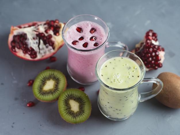 Smoothie sazonal de inverno bebe desintoxicação. dois copos de smoothies verdes e vermelhos. iogurte caseiro de kiwi e romã. conceito de alimentação saudável