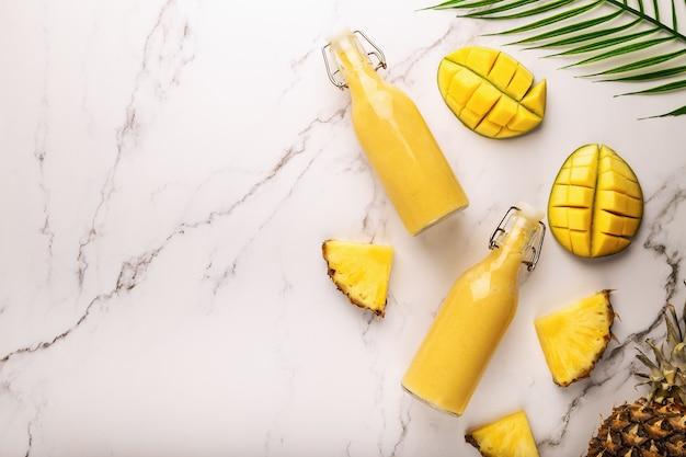 Smoothie tropical fresco com abacaxi e manga em garrafas em mármore. vista do topo.