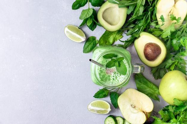 Smoothie vegan verde feito de abacate, pepino, maçã, verduras e limão em um fundo de concreto