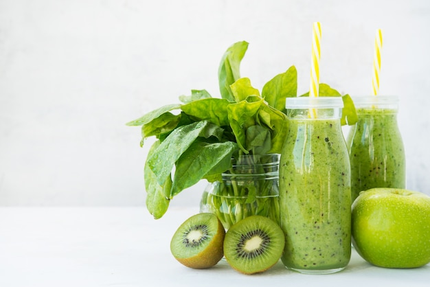 Smoothie vegetariano fresco beber em uma garrafa de vidro de frutas e vegetais verdes. cópia do espaço