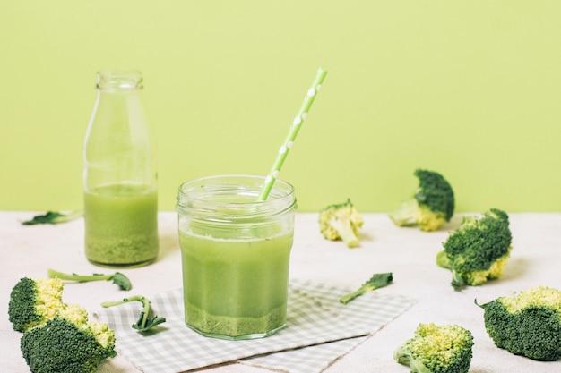 Smoothie verde ao lado de brócolis