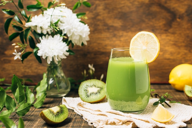 Smoothie verde ao lado do vaso de flores