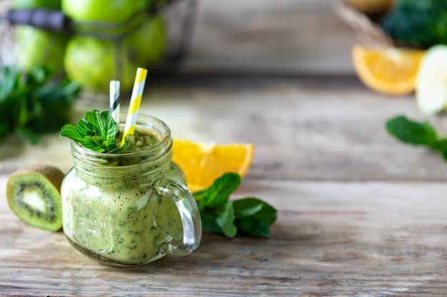 Smoothie verde caseiro em uma jarra com espinafre, laranja, maçã, kiwi e hortelã em uma jarra de vidro e ingredientes. desintoxicação, dieta, conceito de comida saudável e vegetariana. copie o espaço