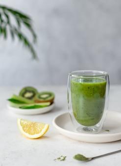Smoothie verde colorido com espinafre, aipo, kiwi, limão e verde superalimento em pó em um copo de parede dupla. comida vegana.