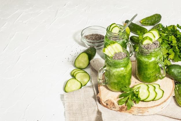 Smoothie verde com pepino em uma jarra de vidro. legumes frescos maduros, verduras e sementes de chia. luz dura na moda, sombra escura. fundo de massa branca, espaço de cópia