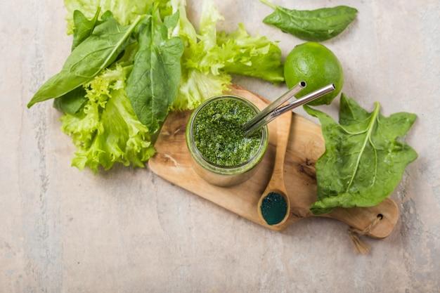 Smoothie verde com spirulina. jovem cevada e chlorella spirulina. superalimento de desintoxicação.