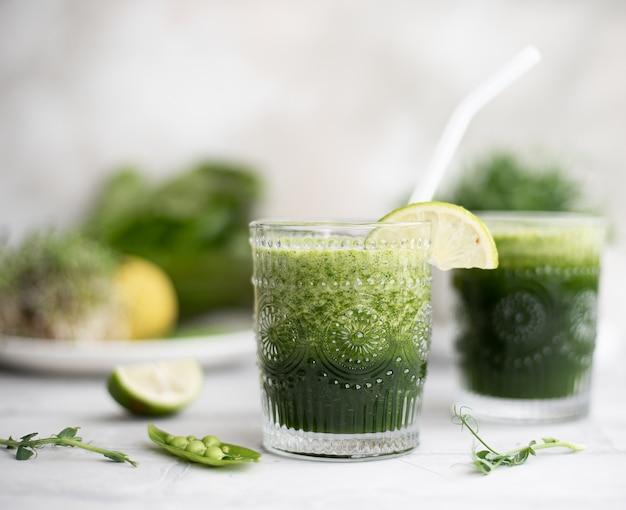 Smoothie verde com verduras frescas e limão em vidro
