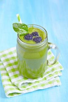 Smoothie verde de espinafre coberto com folhas e amora