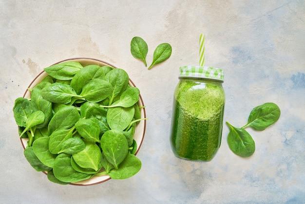 Smoothie verde de espinafre e couve em frasco de vidro e prato com espinafre fresco. copie o espaço.