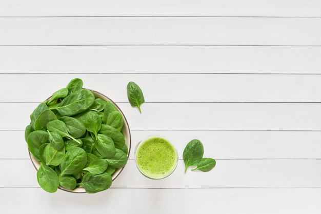 Smoothie verde de espinafre em uma jarra de vidro e prato com espinafre fresco na mesa de madeira branca