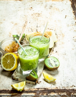 Smoothie verde de kiwi, melão e limão com mel. sobre fundo rústico.