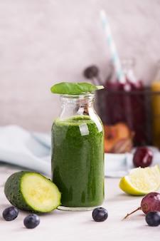 Smoothie verde doce saudável em uma pequena garrafa de vidro