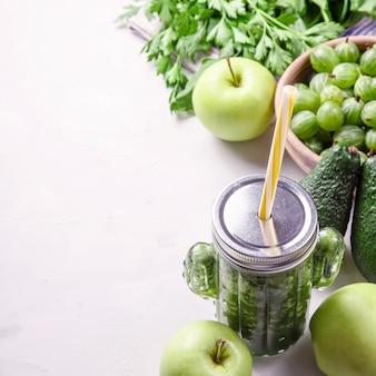 Smoothie verde em um cacto em forma de vidro entre os ingredientes verdes