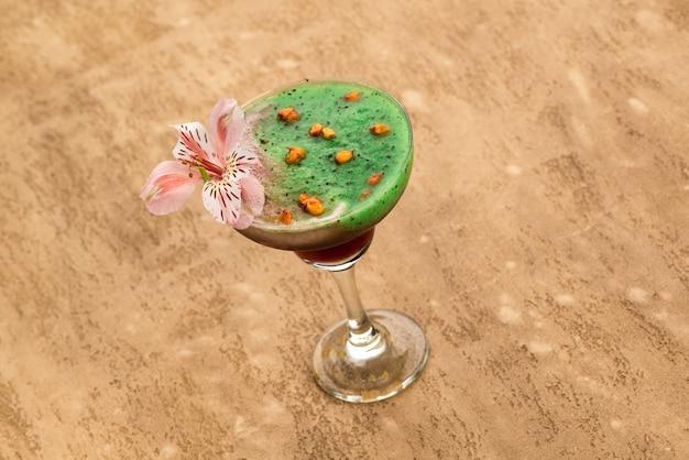 Smoothie verde em um fundo marrom claro