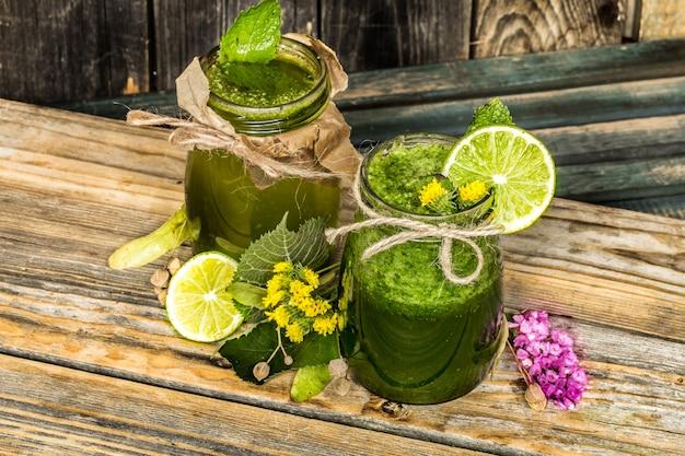 Smoothie verde em uma jarra com limão, kiwi e frutas vermelhas