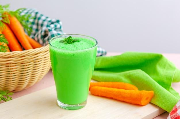 Smoothie verde em vidro sobre fundo de madeira rústico