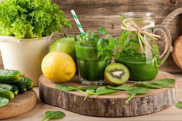 Smoothie verde fresco com ingredientes na mesa de madeira
