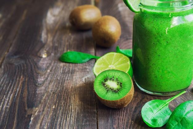 Smoothie verde fresco com kiwi, limão e espinafre em fundo de madeira rústico