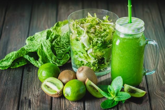 Smoothie verde misturado com ingredientes na mesa de madeira