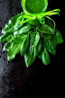 Smoothie verde misturado com ingredientes na mesa preta.