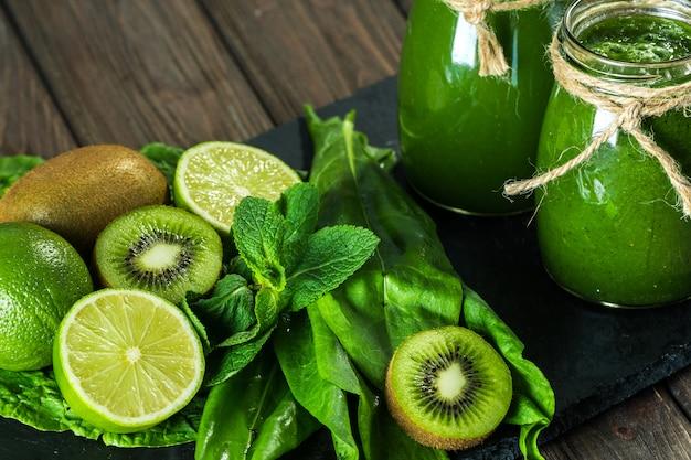 Smoothie verde misturado com ingredientes na placa de pedra, mesa de madeira