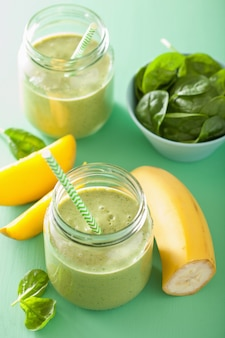 Smoothie verde saudável com banana de manga de espinafre em potes de vidro