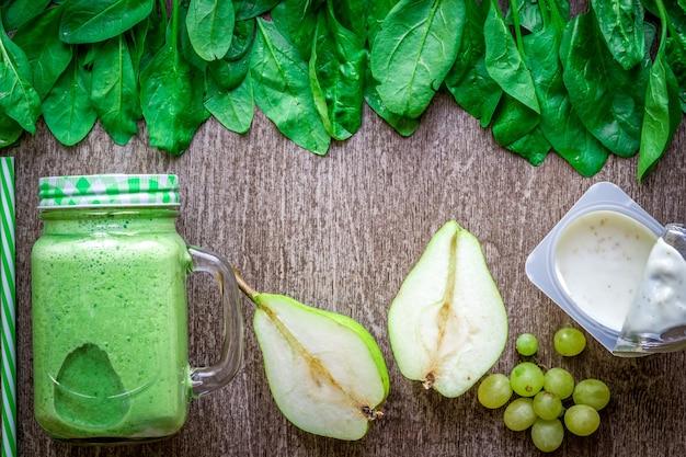 Smoothie verde saudável com espinafre em uma caneca contra fundo de madeira