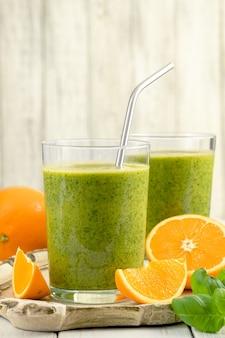 Smoothie verde saudável com espinafre, manga, laranja, limão, maçã, citrone em potes de vidro.
