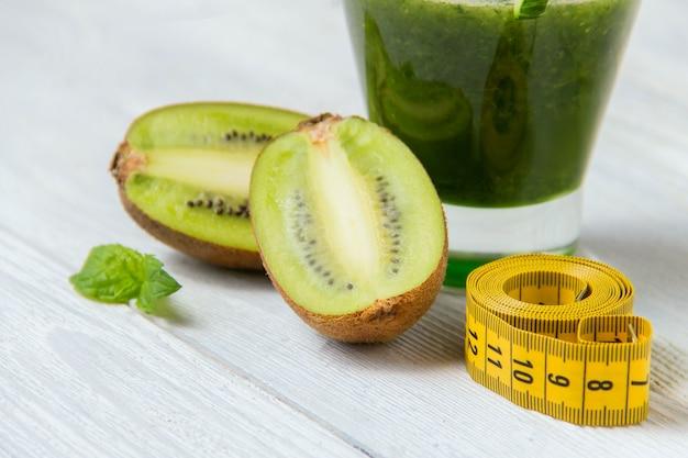 Smoothie verde saudável com ingredientes em fundo branco de madeira