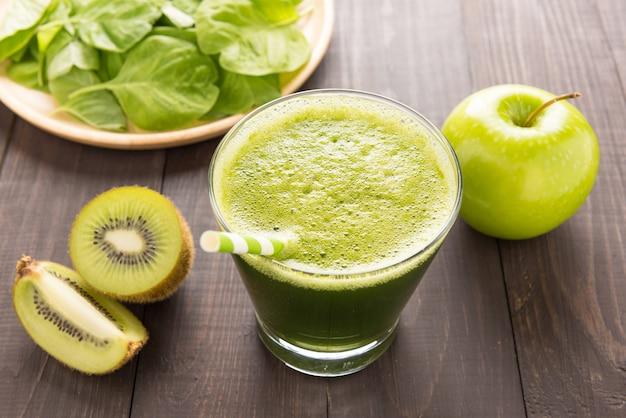 Smoothie verde saudável com kiwi, maçã na mesa de madeira rústica
