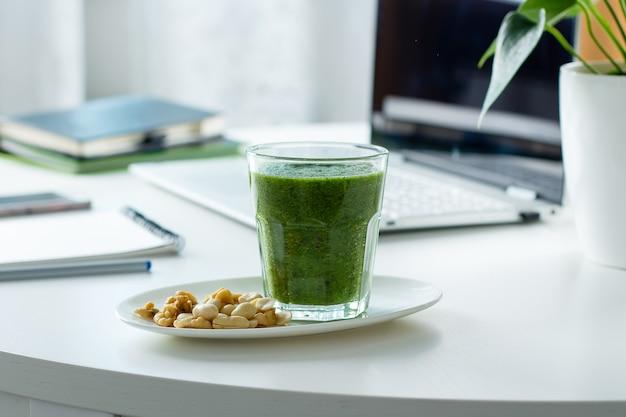 Smoothie verde saudável de espinafre, kiwi e nozes na mesa de trabalho no local de trabalho com laptop