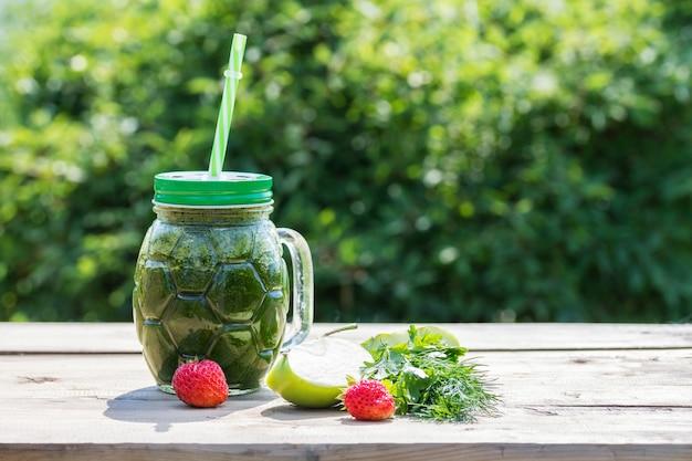 Smoothie verde saudável e ingredientes - salsa, endro, maçã e morango. superalimento. comida saudável de conceito.